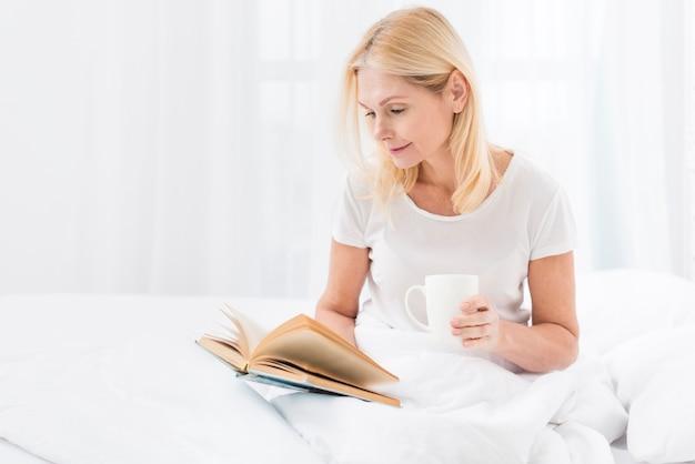 Belle femme senior lisant un livre tout en buvant un café