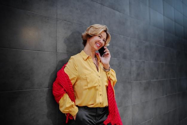 Belle femme senior à la mode blonde caucasienne souriante avec foulard parler au téléphone
