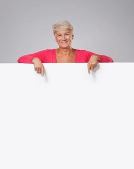Belle femme senior montrant sur tableau blanc vide