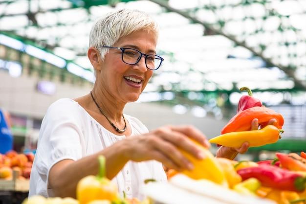 Belle femme senior portant des lunettes achète du poivre sur le marché