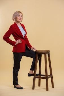 Belle femme senior posant sur une chaise