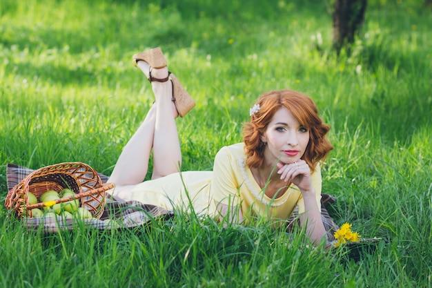 Belle femme sensuelle aux cheveux rouges dans un jardin de printemps