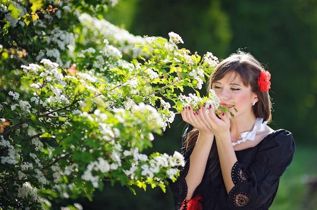 Belle femme sent les fleurs blanches dans le parc du printemps