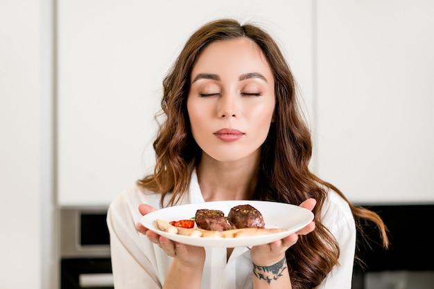Belle femme sent la viande fraîchement cuite dans la cuisine