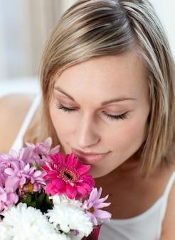 Belle femme sentant un bouquet de fleurs