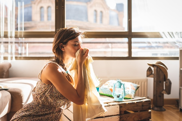 Belle femme sentant son vêtement à la maison.