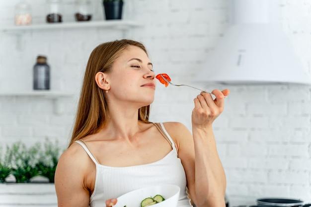 Belle femme sentant la tomate coupée sur la fourche.