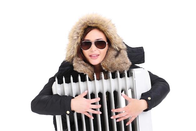 Une belle femme serrant un radiateur sur fond blanc