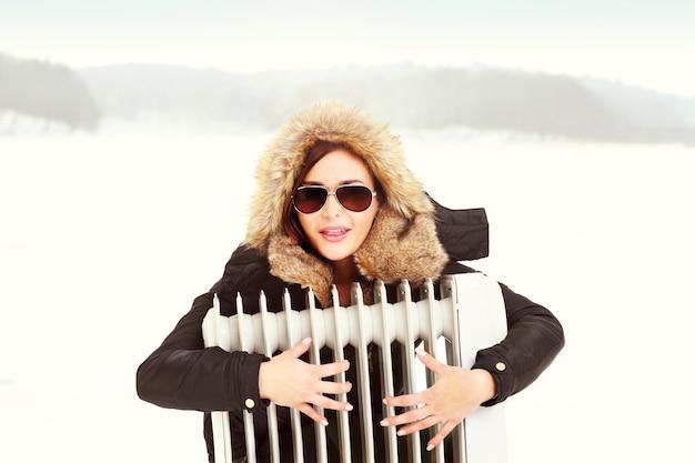 Une belle femme serrant un radiateur en hiver