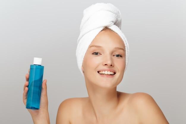 Belle femme avec une serviette blanche et une bouteille cosmétique