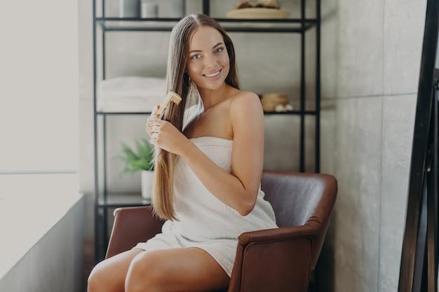 Belle femme en serviette se brosser les cheveux