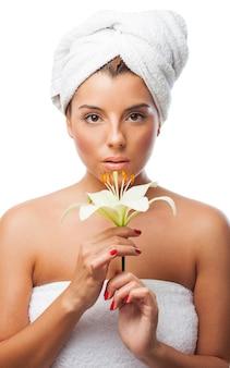 Belle femme avec une serviette tenant lily