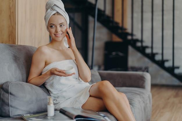 Belle femme avec une serviette sur la tête, appliquer la crème