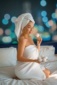 Belle femme avec une serviette sur la tête assise sur le lit et mangeant des biscuits, bonjour