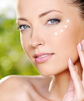 Belle femme sexy appliquant une crème cosmétique sur la peau près des yeux - à l'extérieur