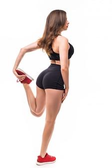 Belle femme sexy brune en tenue de sport noire fait des exercices pour un corps solide