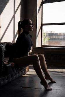 Belle femme sexy sur un canapé en cuir dans une pièce sombre