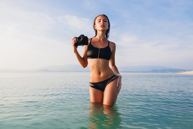 Belle femme sexy, corps mince parfait, peau bronzée, maillot de bain bikini noir, debout dans l'eau bleue, tenant un appareil photo numérique, vacances d'été chaudes et tropicales, tendance de la mode, taille, ventre, hanches
