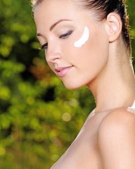 Belle femme sexy avec de la crème cosmétique sur la joue - sur la nature
