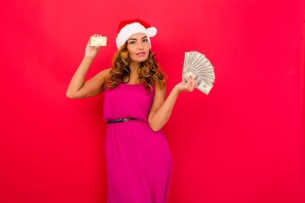 Une belle femme sexy dans un chapeau du nouvel an tenir dans les mains de l'argent et une carte de crédit