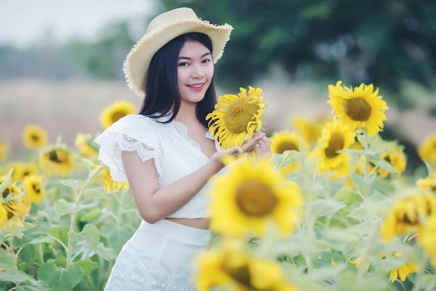 Belle femme sexy dans une robe blanche marchant sur un champ de tournesols