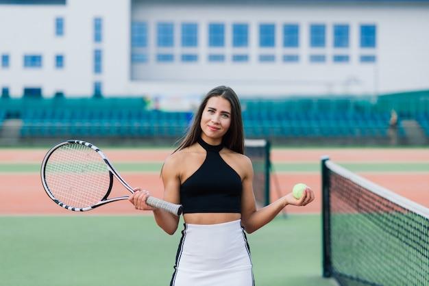 Belle femme sexy élégante dans un vêtement de sport à la mode sur un court de tennis.