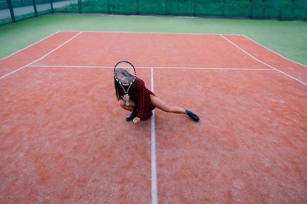 Belle femme sexy élégante dans un vêtement de sport à la mode noir sur un court de tennis.