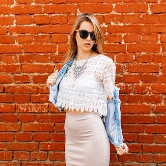 Belle femme sexy jeune hipster dans un chemisier en dentelle blanche et une veste en jean à lunettes de soleil noires dans une jupe beige pose près d'un mur de briques rouges