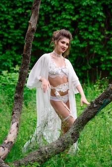 Belle femme sexy en lingerie blanche à l'extérieur.