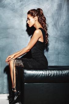 Belle femme sexy modèle dame aux lèvres rouges en robe élégante noire assise sur le canapé près du mur gris