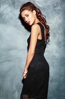 Belle femme sexy modèle femme aux lèvres rouges en robe élégante noire posant près du mur gris