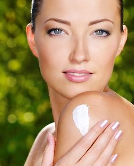 Belle femme sexy avec une peau de santé fraîche appliquant la crème sur l'épaule. en plein air