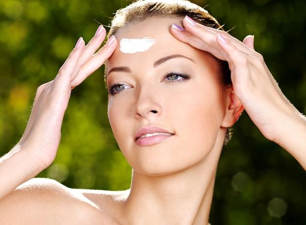 Belle femme sexy avec une peau de santé fraîche appliquant la crème sur le front - à l'extérieur
