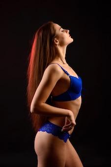 Belle femme sexy en sous-vêtements bleus sur fond sombre, corps féminin parfait, tourné en studio