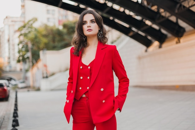 Belle femme sexy de style d'affaires riche en costume rouge marchant dans la rue de la ville, tendance de la mode printemps été