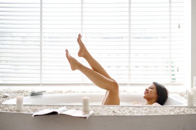 Belle femme, soins de la peau dans le bain avec du lait. personne de sexe féminin dans la baignoire, soins de beauté et de santé au spa, traitement de bien-être dans la salle de bain, cailloux et bougies sur fond