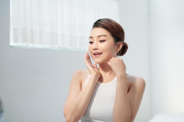 Belle femme de soins de la peau visage souriant à vous isolé sur fond blanc. beauté asiatique
