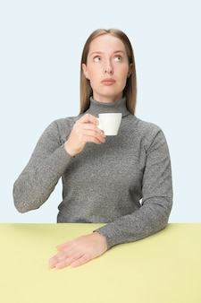 Belle femme solitaire assise au studio bleu et à la triste tenant la tasse de café à la main.