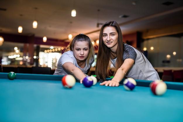 Belle femme avec son amie jouant au billard dans un pub