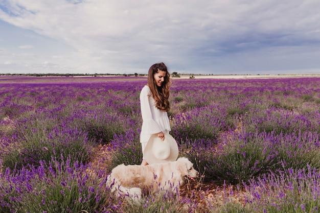 Belle femme avec son chien golden retriever dans les champs de lavande au coucher du soleil.
