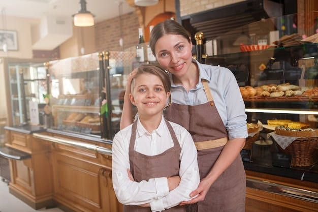 Belle femme et son jeune péché portant des tabliers, travaillant ensemble dans leur magasin de pain familial