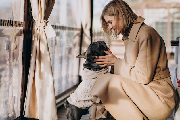 Belle femme avec son mignon bouledogue français en tenue chaude