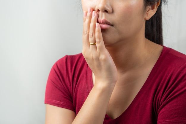 Belle femme souffrant de maux de dents, de carie dentaire ou de sensibilité. concept de soins de santé des femmes