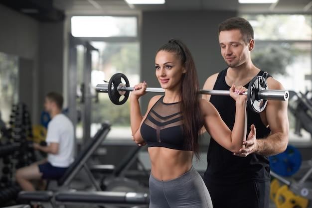 Belle femme soulevant des haltères et entraîneur posant dans une salle de sport.