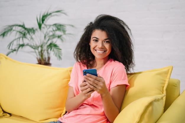 Belle femme souriante à l'aide de smartphone, achats en ligne, communication, assis à la maison