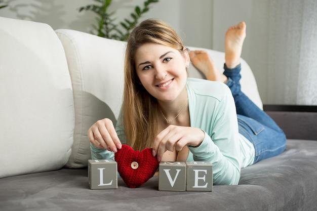 Belle femme souriante allongée sur un canapé et faisant le mot
