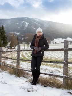 Belle femme souriante appuyée contre une clôture en bois sur une ferme des hautes terres dans les alpes
