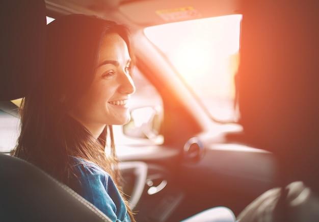 Belle femme souriante assise sur la banquette arrière de la voiture.