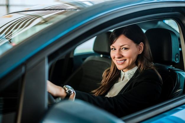 Belle femme souriante assise dans une voiture neuve.