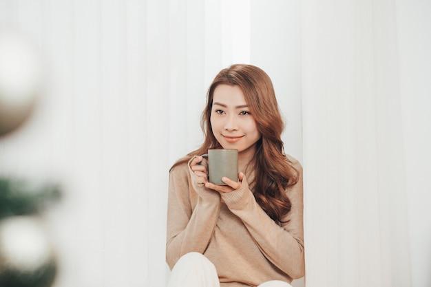 Belle femme souriante assise à la maison avec une tasse de café sur fond de lumières.
